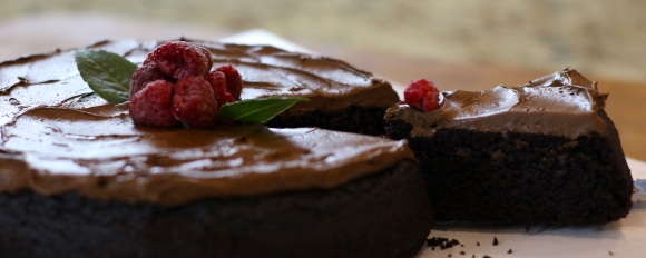 Cutting a slice of this beautiful Quinoa Chocolate Cake with a raspberry on top.
