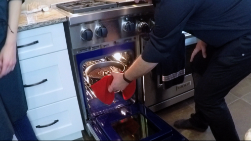 """Pulling the cake from the Beautiful Wolf 48"""" Range oven."""