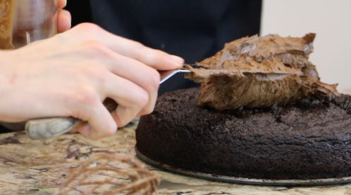 Spreading the perfectly textured coconut-oil frosting on top.